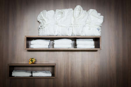 white bathrobes and towels stapled on brown wooden shelf with flowers