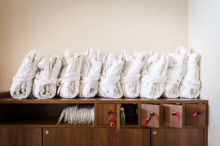 luxury goods: arranged white bathrobes on cupboard with wooden lockable boxes