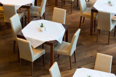 floor cloth: laid table with cloth and leather chairs on wooden floor Stock Photo