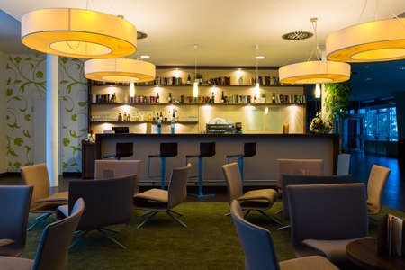 bar counter: nice hotel lounge bar with bottle shelfs and seats, tables, lights