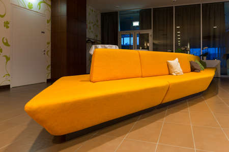perspective of huge yellow orange sofa in hotel lobby photo
