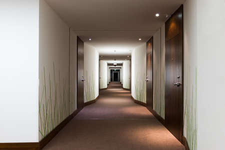 long hotel corridor with doors and green grass wallpaper Stock Photo
