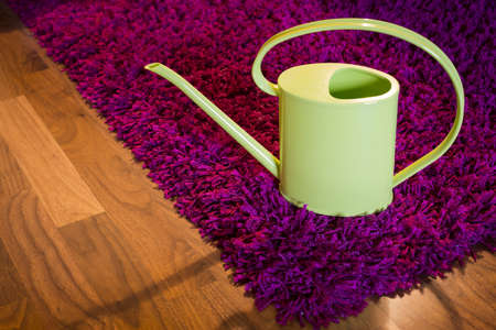 watering can on wooden and purple carpet photo