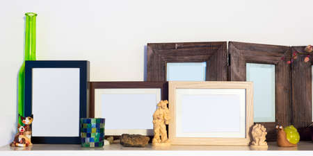 several wooden pictures frames standing on shelf photo