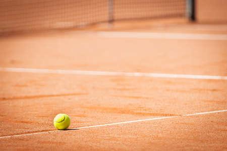 gele tennisbal op oranje zand en witte lijnen Stockfoto