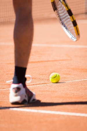 tennis clay: sportsman catchs up his tennis ball with racket