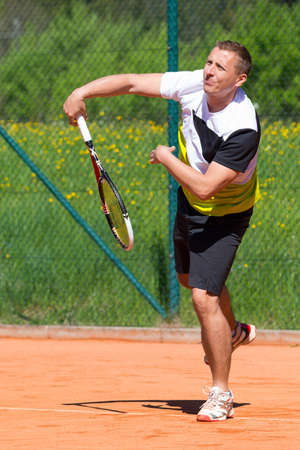 tennis clay: tennis player after hitting service ball