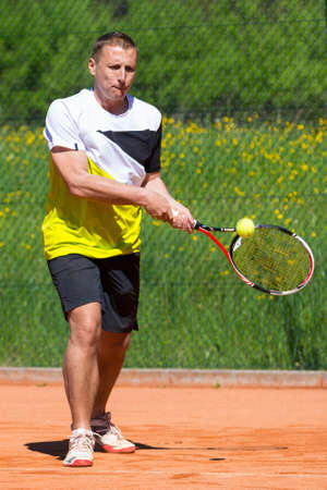 backhand: tennis backhand with ball on racket on sand court Stock Photo