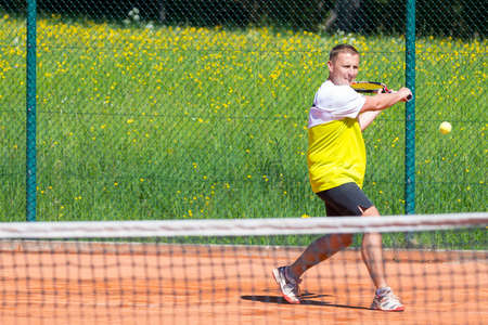slice backhand of tennis player behind net photo