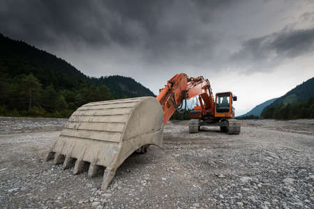 perspective of digger power shovel in red on gravel photo