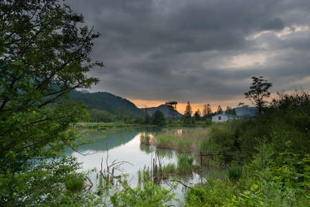 stormy weather over swamp with bird tower photo