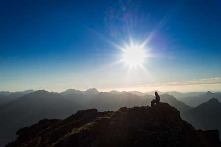 lonely sad girl sitting on rock at sunset mountains Standard-Bild