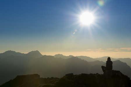 eenzaam denkend mens op de piek van de berg bij zonsondergang
