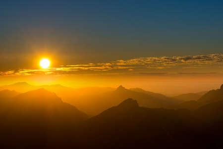silhouet van een aantal bergtoppen bij humeurig zonsondergang met wolken