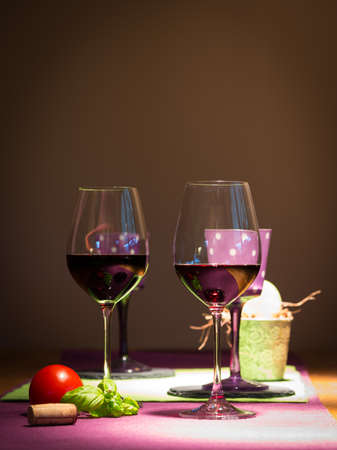 two redwine glasses with tomato and basil on table for couple photo