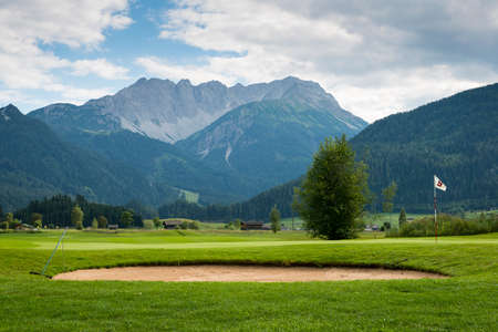 country club: golf course with sand bunker and hole flag in mountain landscape