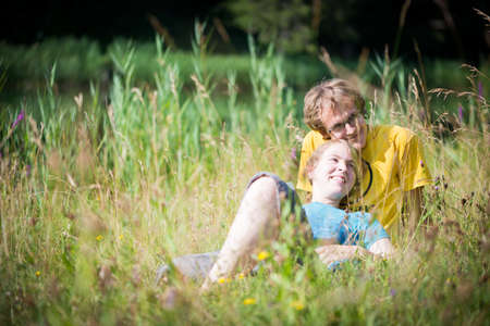 young lovely couple lying in high grass having fun in summer photo