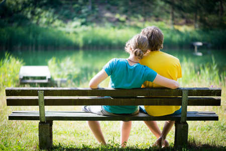 love seat: lovely young couple sitting on seat bench with view to lake Stock Photo