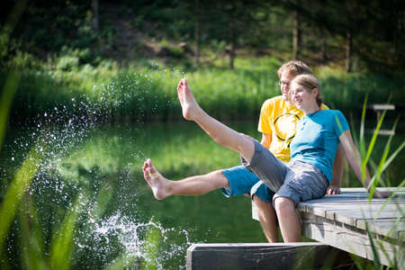 young couple splashing water at lake sitting on wooden peer photo