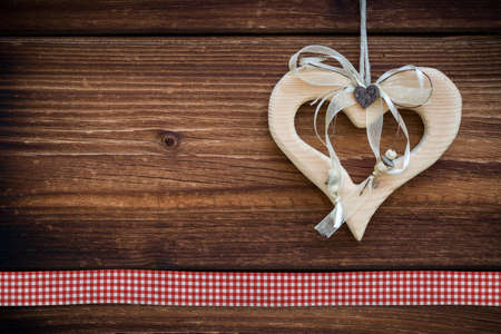 clipped wooden heart hanging on sun burned wood planks with stitch photo