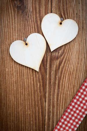 vertical wooden plank with two lovely hearts and checked ribbon photo