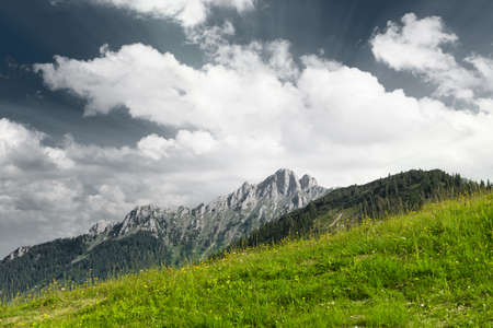 green mountain meadow with mountain peak and clouds photo