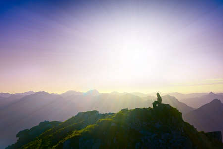 lonely sad girl sitting on mountain summit looking over alps Stock Photo