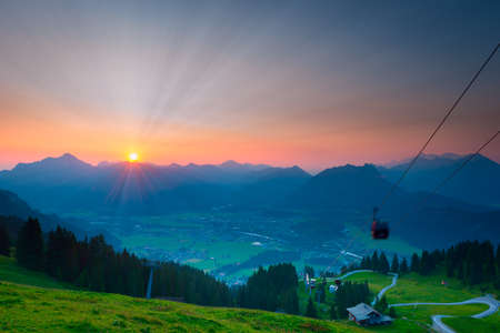 sunbeams while sunrise in austrian mountains with ropeway photo