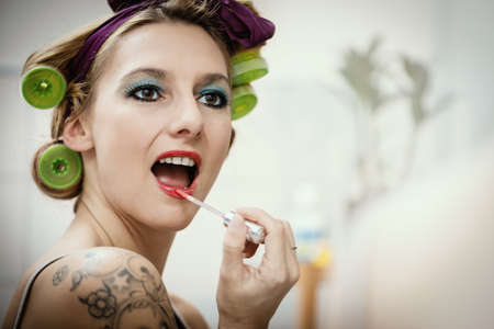 young attractive woman with hair roller is painting her lips Stock Photo - 26317545