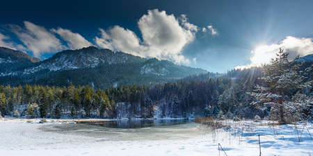 shining through: small frozen lake in austrian alps with sun shining through clouds Stock Photo