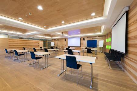 moderne houten zaal met tafels een stoelen en projectiescherm
