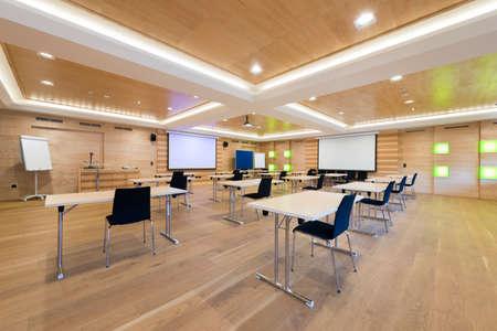 tafels en stoelen in moderne houten conferentieruimte met projectieschermen