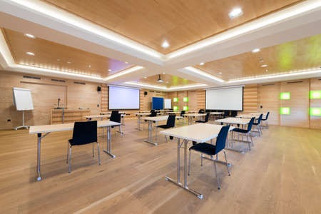 tables and chairs in modern wooden conference room with projection screens
