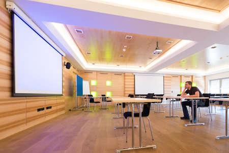 homme Desperated dans la salle de conférence avec écran de projection blanc