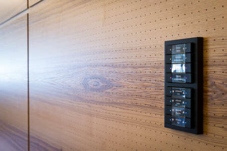 switches: black switches for light control on wooden acoustic wall Stock Photo