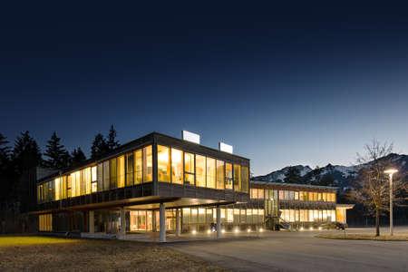 verlichte moderne houten kantoorgebouw 's nachts Stockfoto