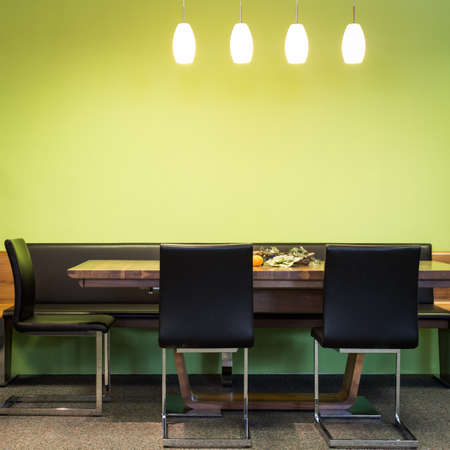 modern dining room: cantilever chairs at timber table with lamps and green wall Stock Photo