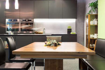microondas: mesa de comedor con sillas de cuero y cocina moderna de color gris oscuro