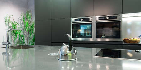 detail over work plate of modern kitchen with teapot and baking oven photo
