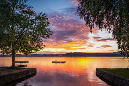 moody sunset at lake wallersee in austria with trees and wooden platform photo