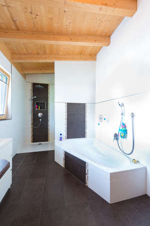 bath with bathtub in timber house and dark brown tiles floor photo