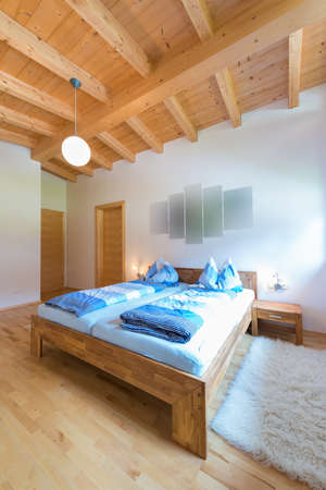vertical shot of wooden bed in bedroom at timber house photo