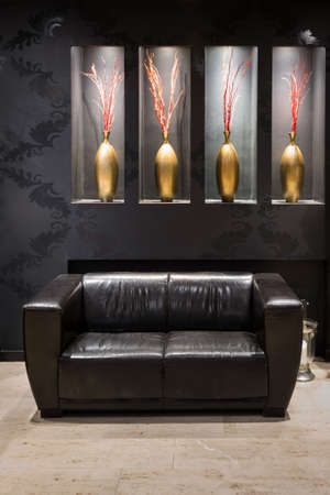 vestibule: black leather couch in anteroom with golden flower vase