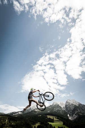 young trick stunt biker jumps trick high over alp mountains