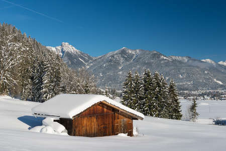 old barn in winter: snow landscape in austrian alps with wooden timber shed