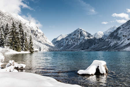 quiet scenery: idyllic cold lake at snow mountain landscape in winter scenery