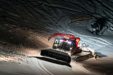 snow grooming machine: night shot of red snow groomer at work in austria Stock Photo