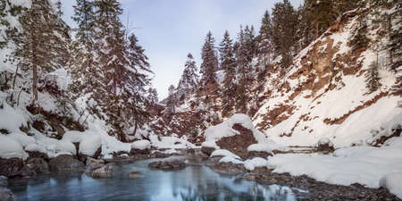 small river between stones and snowy rocks in winter photo