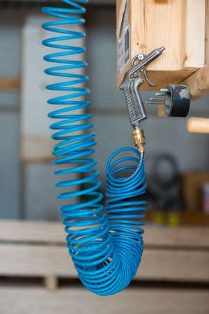 blue compressed pneumatic air hose with pistol hanging at screw