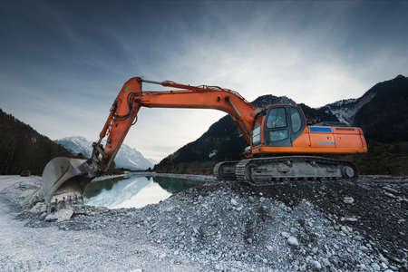 湖の前に砂利石の上に立って大きなシャベル掘削機 写真素材